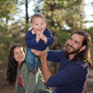 Young family having fun in nature shallow DOF baby's face in focus